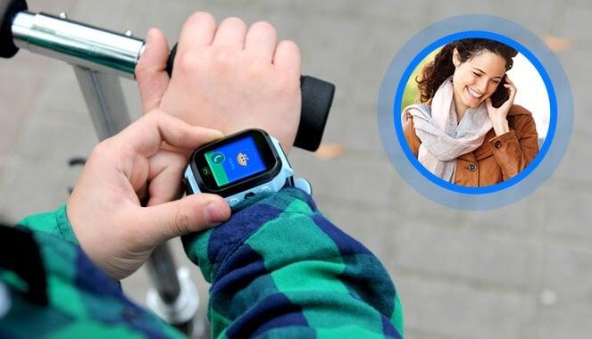 Ręka dziecka w koszuli w zielono granatową kratę, na której jest zegarek od Bezpiecznej Rodziny GJD.10, a obok małe zdjęcie kobiety w brązowych włosach i brązowej kurtce, rozmawiającej przez telefon