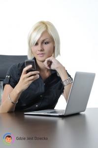 Lokalizowanie bliskiego w usłudze Gdzie Jest Dziecko, czyli krótkowłosa blondynka w ciemnej koszuli siedzi nad otwartym laptopem i zagląda w telefon komórkowy
