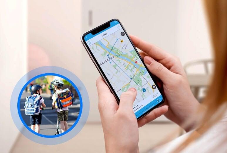 Funkcja lokalizacji w telefonie na rękę GJD.06, czyli kobieta trzymająca w dłoniach telefon z aplikacją Gdzie Jest Dziecko, na której widać mapę z zaznaczonymi miejscami, w których przebywał bliski oraz miniatura przedstawiająca dwóch chłopców jadących w ciepły dzień z kaskami i plecakami szkolnymi na hulajnogach