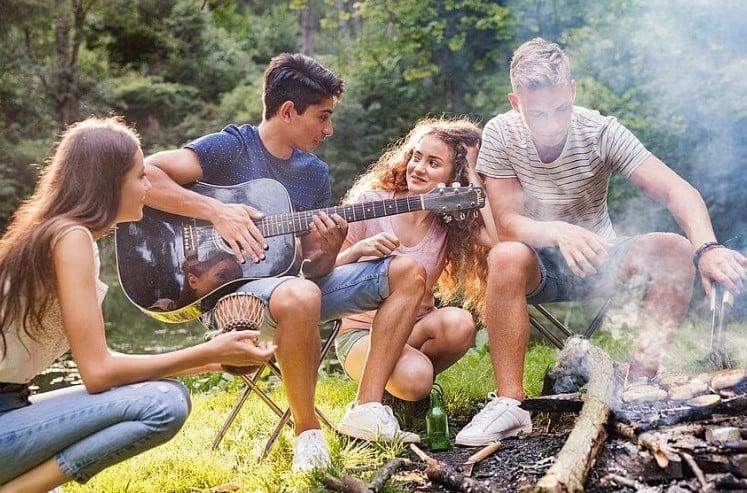 Nastolatki na ognisku, czyli dziewczyna z długimi włosami kucająca przy ognisku, chłopak z ciemnymi włosami w granatowej koszulce i krótkich jeansach siedzący na stołku i trzymający gitarę, kucająca obok niego dziewczyna z długimi kręconymi włosami w różowej koszulce oraz blondyn w koszulce w paski i w krótkich jeansach układający jedzenie na ognisku w lesie