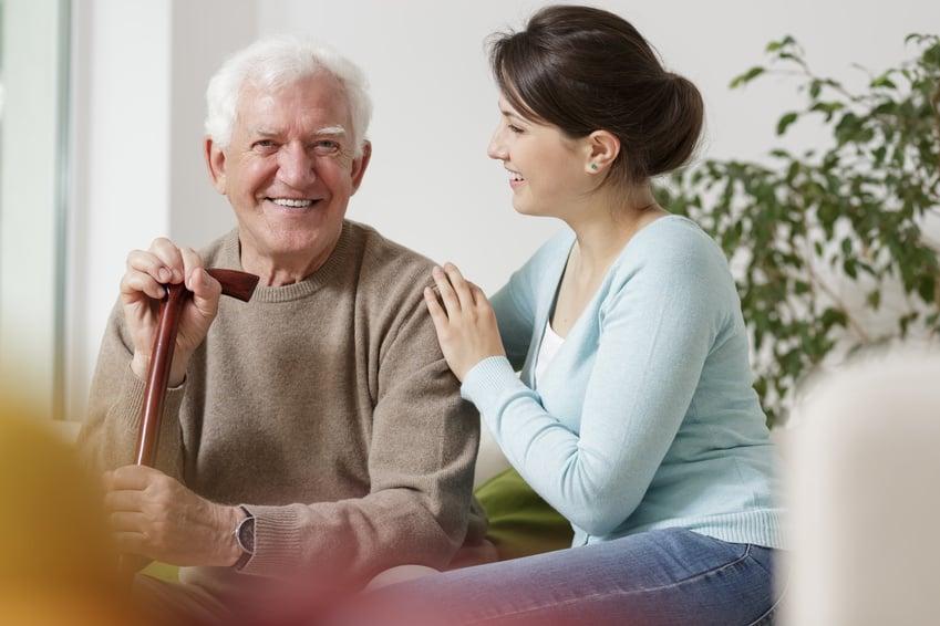 Uśmiechnięty starszy mężczyzna z siwymi włosami siedzi na sofie opierając się o drewnianą laskę, a obok siedzi obejmująca go młoda brunetka w niebieskim swetrze i jeansach