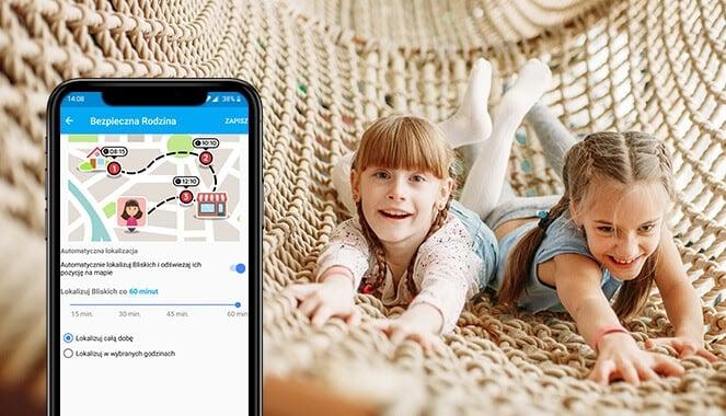 Dokładna lokalizacja dzieci z Bezpieczną Rodziną, czyli dwie kilkuletnie uśmiechnięte dziewczynki w długich warkoczach bawiące się na dużym hamaku z jasnej, grubej włóczki oraz widok aplikacji od Bezpiecznej Rodziny z możliwością lokalizowania dziecka