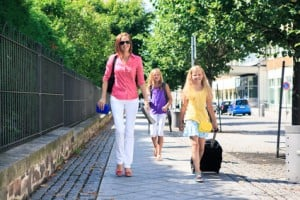 two teenage girls and their mother on the way to school