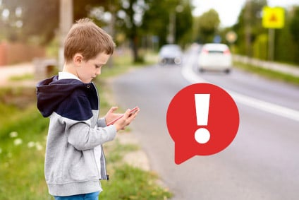 Dziecko grające w Pokemon GO przy ulicy, czyli kilkuletni chłopiec ubrany w szarą bluzę, stoi tuż przy trasie samochodowej i patrzy w telefon