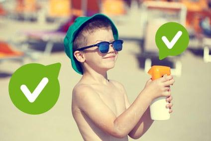Dziecko na plaży, czyli chłopiec bez koszulki z okularami przeciwsłonecznymi i niebieskim kapeluszem, trzymający w dłoni płyn do opalania