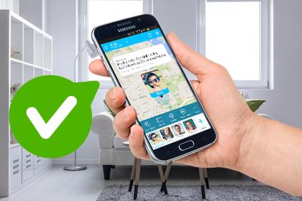 Aplikacja Gdzie Jest Dziecko, czyli wyciągnięta dłoń na tle jasnego mieszkania, trzymająca ciemny telefon komórkowy, na którym widoczny jest screen z aplikacji z mapą i podaną lokalizacją dziecka