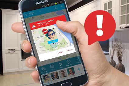 Widok jasnych mebli, na tle których widoczna jest dłoń trzymająca telefon komórkowy, na którym jest screen z aplikacji Rodzinne S.O.S z mapą i lokalizacją dziecka oraz ikona wykrzyknika w czerwonej chmurce