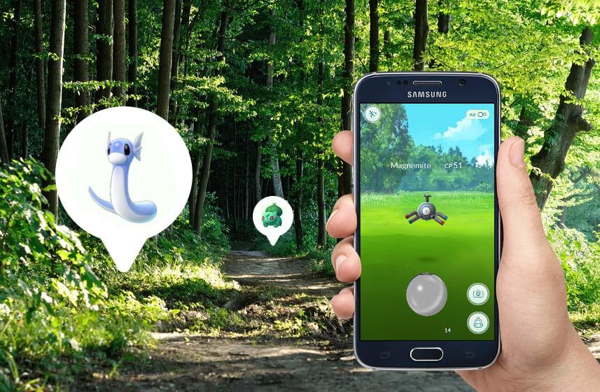 Widok ścieżki w lesie i zaznaczone na niej dwie postacie w białych dymkach z gry Pokemon GO oraz dłoń trzymająca ciemny telefon komórkowy ze screenem z gry