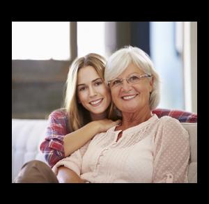 Babcia z wnuczką, czyli starsza kobieta z siwymi włosami, w okularach i jasnej bluzce siedzi na fotelu, a za nią przytulona do niej siedzi młoda dziewczyna z jasnymi długimi włosami ubrana w koszulę w kratę i obejmuje seniorkę ręką