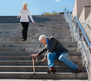Starszy mężczyzna siedzi na schodach od wysokiego budynku i próbuje się podnieść oraz zbiegająca do niego kobieta w krótkich siwych włosach ubrana w białą bluzkę i ciemne spodnie