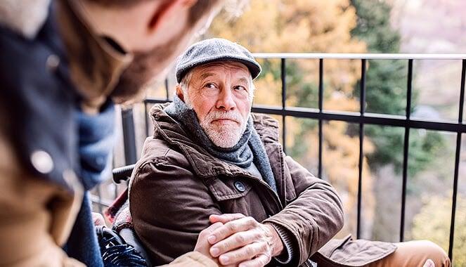 Powiadomienie SOS w opasce dla seniora, czyli starszy mężczyzna ubrany w ciemną kurtkę i kaszkiet, siedzi na wózku inwalidzkim i trzyma za rękę pochylającego się nad nim młodego mężczyznę